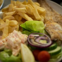 Crispy grilled fish with salad and chips